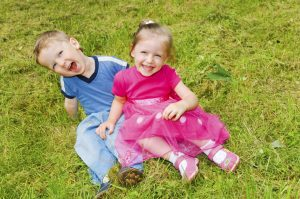 laughing small boy and girl sitting on green grass in the park