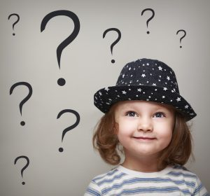 Happy thinking kid girl in hat looking up on questions